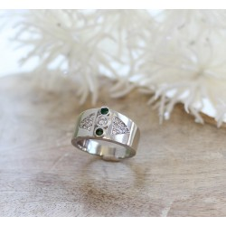 Bague en or blanc avec diamant central et emeraudes
